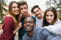 Multiracial group of friends taking selfie in a urban park with a black men in foreground Royalty Free Stock Image