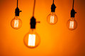 Multitude of bulb lamps on orange background Royalty Free Stock Photos