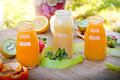 Multivitamin fruit juices and juice ingredients on table Royalty Free Stock Photo
