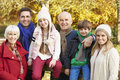 Multl generation family by wooden fence on autumn walk Royalty Free Stock Photo
