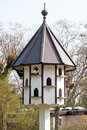 Multystoried birdhouse funny starling house on spring park background Stock Photos