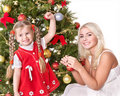 Mum with a daughter decorate christmas tree. Stock Photo