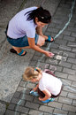 Mum and daughter drawing with chalk overhead view of mother preschool on pavement or sidewalk colorful Stock Photos
