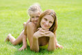 Mum and daughter lie on green lawn in a bikini and look in the frame