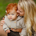 Mum gently embraces the redhead baby girl on autumn forest backg Royalty Free Stock Photo