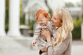 Mum gently embraces the redhead baby girl and laughing in autumn Royalty Free Stock Photo