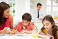 Mum helps children with homework as dad works in background Royalty Free Stock Image