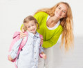 Mum helps her daughter get ready for school mother mom support child to wear a backpack Royalty Free Stock Photos