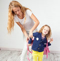 Mum helps her daughter get ready for school mother mom support child to wear a backpack Stock Images