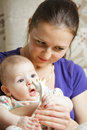 Mum with her baby on hands both looking sideways Royalty Free Stock Images