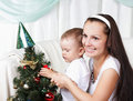 Mum and her daughter decorate a christmas fur-tree Stock Images