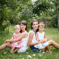Mums and kids two young two little girls sitting on grass looking at camera Royalty Free Stock Photography