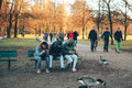 Munich, Germany, December 29, 2016: Friends sit on a bench in the English Garden in Munich one of the largest city parks Royalty Free Stock Photo