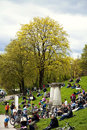 Munich germany people sitting leisurely on the green outdoors a festive day of spring lawn and stairs at bavaria park with view of Royalty Free Stock Photo