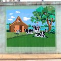 Mural of a young blonde girl riding a dairy cow on a bridge underpass on james rd in memphis tn woman sitting field Stock Images