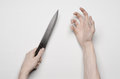 Murder and Halloween theme: A man's hand reaching for a knife, a human hand holding a knife isolated on a gray background in studi Royalty Free Stock Photo