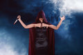 Murderer asian witch woman with red cloak holding bloody knife Royalty Free Stock Photo
