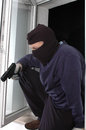 Murderer with the handgun in balaclava is entering Royalty Free Stock Photos