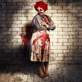 Murderous monster clown standing in full length on brick illustration background with blood stained apron killing medical practice Stock Image