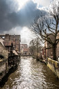Murky canal meandering through medieval bruges under a cloudy sky Stock Photography