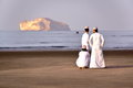 MUSCAT, OMAN - FEBRUARY 9, 2012: Three Omani men traditionally dressed on the main beach in Central Muscat