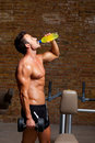 Muscle man at gym relaxed with energy drink Stock Photo