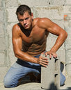 Muscle sexy naked dirty young worker with block Royalty Free Stock Photo