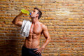 Muscle shaped man at gym relaxed drinking Royalty Free Stock Photo