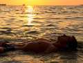 Muscle wet sexy naked man lying in sea water Royalty Free Stock Photo