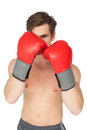 Muscly man wearing red boxing gloves in guard position on white background Royalty Free Stock Photos