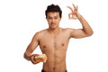 Muscular asian man load carbs with some bread show ok isolated on white background Royalty Free Stock Image