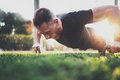Muscular athlete exercising push up outside in sunny park. Fit shirtless male fitness model in crossfit exercise Royalty Free Stock Photo