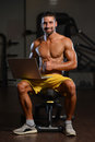 Confident Muscled Man In Gym Using Laptop