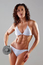 Muscular athletic young woman fitness muscular body in a white bathing suit on a gray background with dumbbells in hand abdominal Stock Image