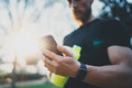 Muscular bearded athlete checking burned calories on smartphone application after good workout outdoor session on city Royalty Free Stock Photo