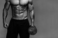 Muscular bodybuilder guy close up monochrome of doing exercises with weights over grey background black and white Stock Image