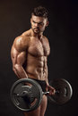 Muscular bodybuilder guy doing exercises with big dumbbell over black background Stock Photography
