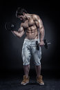 Muscular bodybuilder guy doing exercises with dumbbells over black background Royalty Free Stock Images
