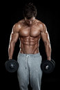 Muscular bodybuilder guy doing exercises with dumbbells over black background Royalty Free Stock Image