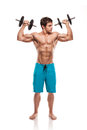 Muscular bodybuilder guy doing exercises with dumbbells over whi white background Royalty Free Stock Images