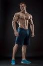 Muscular bodybuilder guy doing posing over black background Royalty Free Stock Photo
