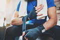 Muscular Boxer man prepairing hands for hard kickboxing training session in gym. Young athlete tying black boxing Royalty Free Stock Photo