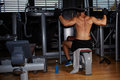 Muscular build athlete exercising on pulldown weight machine back view of Royalty Free Stock Photography