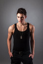 Muscular built man with a dog tags good looking on black background Stock Image