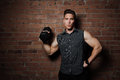 Muscular guy doing exercises with dumbbell against a brick wall Royalty Free Stock Photo