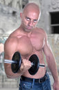 Muscular guy doing exercises with dumbbell outdoor Royalty Free Stock Photography