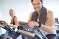 Muscular guy on elliptical bike smiling at camera handsome young the while exercising with his partner next to him inside the Stock Photos