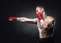 Muscular kickbox or muay thai fighter punching. Royalty Free Stock Photo