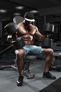 Muscular man with big dumbbells working out in gym, doing exercise Royalty Free Stock Photo