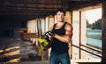 Muscular man with a chainsaw on the ruins Stock Image